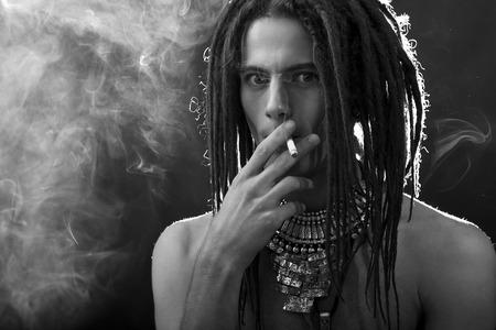 dreadlocks: Retrato de hombre joven. Chico guapo con estilo con rastas y un cigarrillo y una variedad de elegantes joyas de plata y rastas - Cara de primer plano