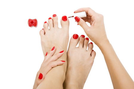 pedicure process - red manicure and pedicure, isolated. female foot with red pedicure photo