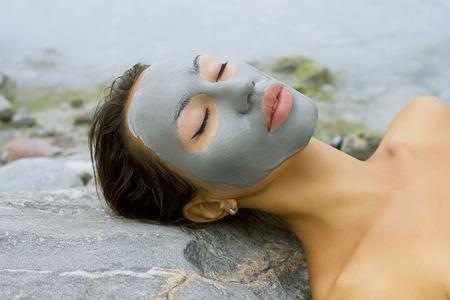 스파 야외, 아름 다운 젊은 여자는 그녀의 얼굴에 자연 죽은 바다 얼굴 마스크 거짓말.