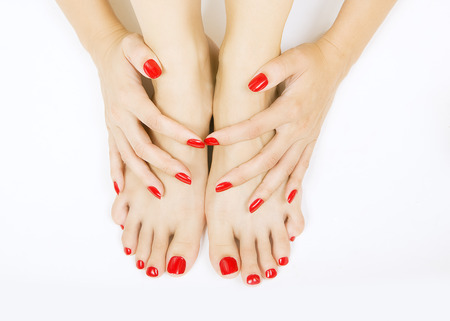 manicure and pedicure: female foots with red pedicure and hands with red manicure