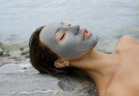 屋外スパ、美しい若い女性が彼女の顔に自然死海フェイシャル マスクで横になっています。