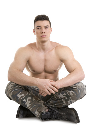 young knife: attractive soldier with athletic body sitting over white background