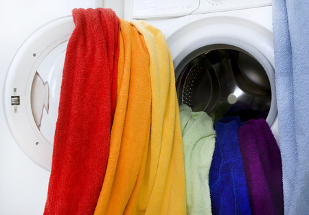 Washing machine and colorful laundry to wash (creative concept)