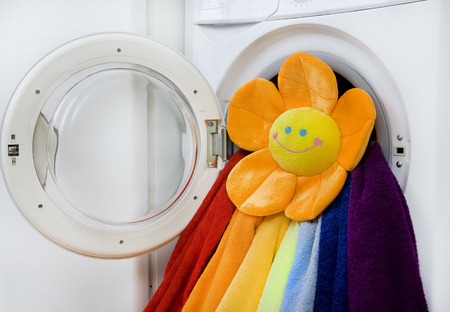 launderette: Washing machine, toy and colorful laundry to wash