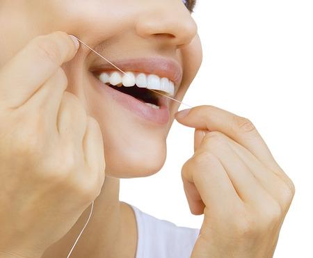 higiene: La mujer y el hilo dental los dientes - mujer cauc�sica joven usando la seda dental (close up mujer de la sonrisa) Foto de archivo