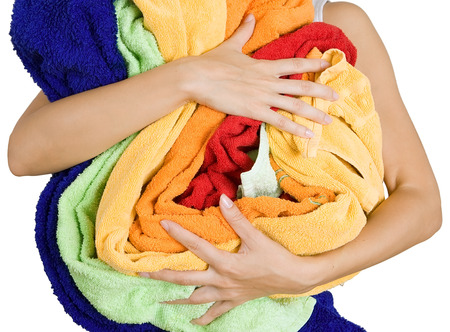 Woman holding a lot of colorful laundry in her hands, a lot of housework, Isolated on white