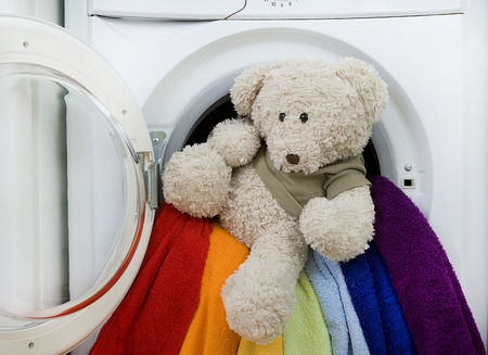 lave: childrens toy and colorful laundry to wash in Washing machine Stock Photo