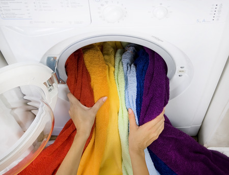 woman taking color laundry (clothes) from washing machine