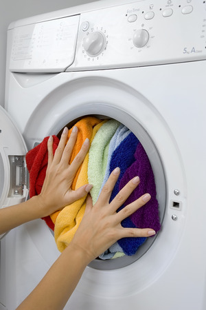 woman loading clothes in the washing machine Stock Photo