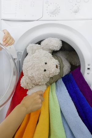 lavadora con ropa: mujer teniendo juguete esponjoso de lavadora Foto de archivo
