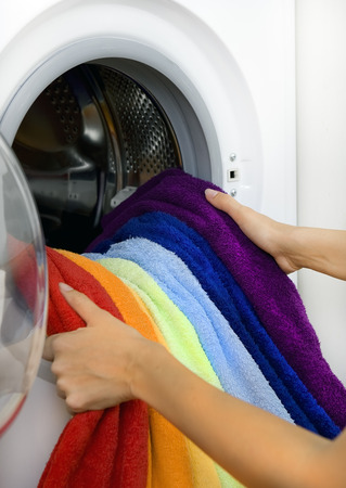 launderette: woman taking color clothes (laundry) from washing machine
