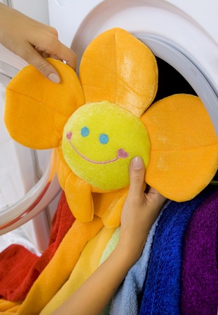lave: woman taking fluffy childrens toy from washing machine