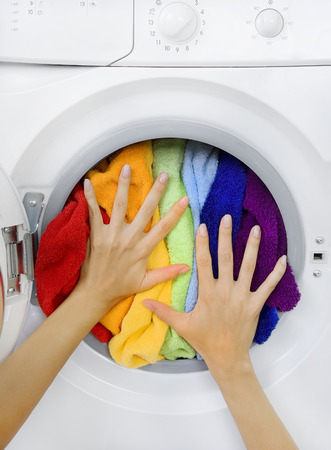 woman loading clothes (colorful laundry) in the washing machine Stockfoto