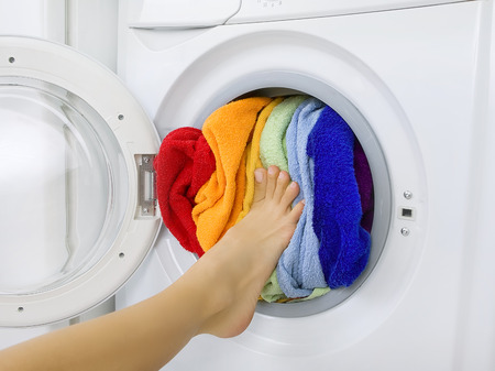 launderette: woman loading colorful laundry (clothes) in the washing machine