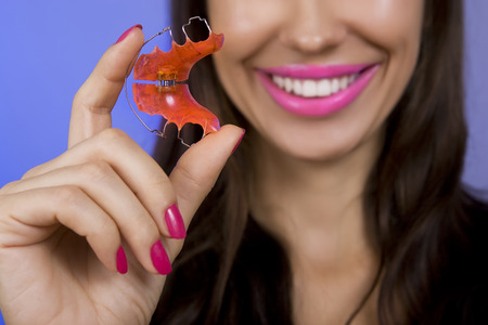 Beautiful smiling girl with retainer for teeth, blue  photo