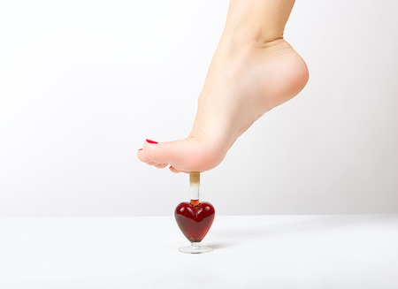 Sexy female leg stepping on the red heart photo