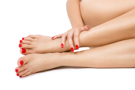 manicure and pedicure: Beautiful long female bare sexy legs with red pedicure, female foots with red pedicure and hands with red manicure close up, isolated