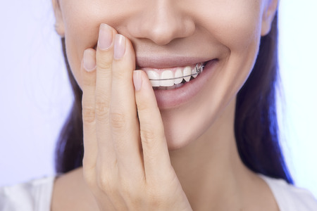 Portrait of Beautiful smiling girl covering with hand her retainer for teeth photo