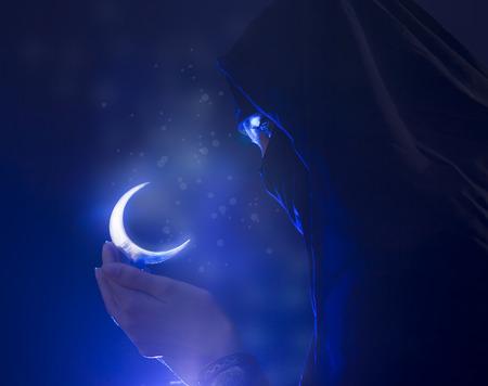 islamic prayer: Beautiful young muslim girl with hijab and jewelry holding a moon symbol, spirituality