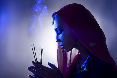 Beautiful young indian woman in traditional clothing with incense and oriental jewelry. Beautiful Girl praying (blue lens effect) 版權商用圖片 - 32260169