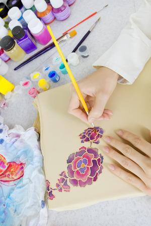batik motif: Batik process: artist paints on fabric, Batik-making. An artist paint the floral motif on a batik fabric Stock Photo
