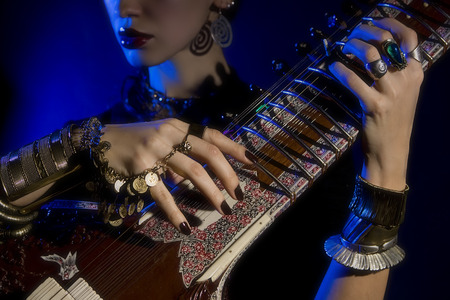 stringed: Beautiful young indian woman in traditional clothing with sitar and oriental jewelry. Beautiful bollywood Girl playing the sitar (blue lens effect) Stock Photo