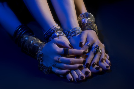 oriental jewelry: female feet and hands with beautiful national indian jewellery, tribal style