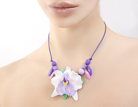 clay modeling: polymer clay jewelery: beautiful woman with a floral orchid necklace around her neck, vintage accessories Stock Photo