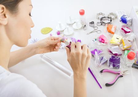 Artiste crée des bijoux à partir d'argile polymère, artiste au travail. Atelier Banque d'images - 33989443