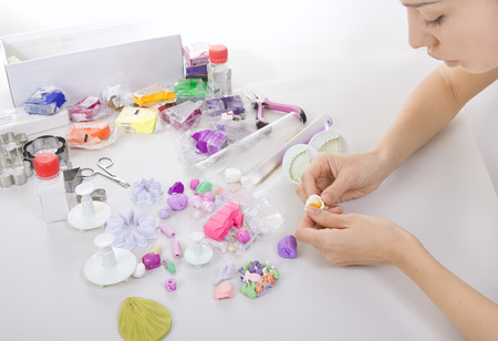 Artist makes jewelry from polymer clay, artist at work. Workshop photo