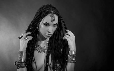 Fashion Beauty. Mystic Make-up. Beautiful Woman With Luxury glossy Makeup and stylish hair (dreadlocks) . Beautiful sensitive Girl Face, indian accessories (oriental jewelry). black and white