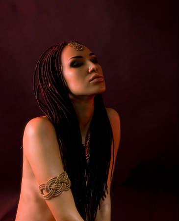 Beauté Mode. Mystic orientale Make-up. Belle femme avec luxe brillant Maquillage d'or et les cheveux de style (des dreadlocks). Beautiful Girl sensibles Visage, accessoires indiens (bijouterie oriental) Banque d'images - 34666131