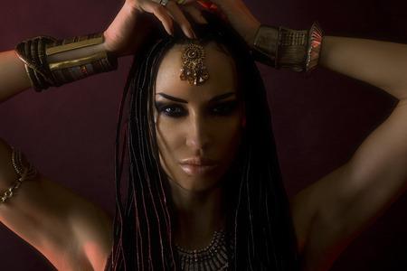 cornrows: Belleza Moda. Mystic maquillaje. Hermosas Womans con el lujo brillante maquillaje oro y pelo con estilo (rastas). Cara hermosa chica sensible, accesorios Foto de archivo