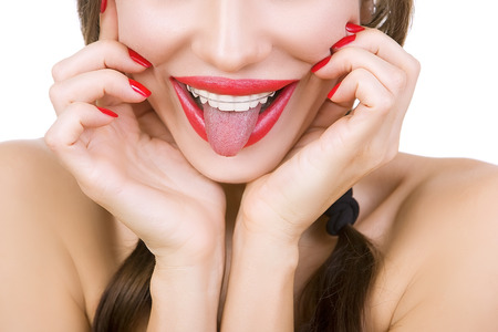 lengua afuera: Bella joven sonriente con retenedor para los dientes y con lápiz labial rojo sacando la lengua, primer plano