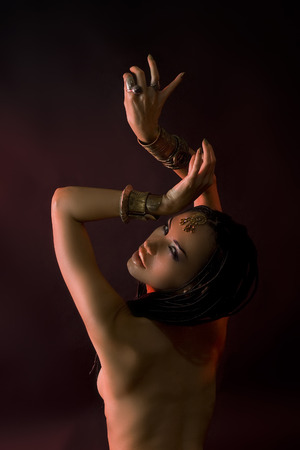 Fashion Beauty and stylish hair (dreadlocks). Spirituality dance. Beautiful Sexy Woman With Luxury glossy gold eastern Makeup danceing tribal fusion. Indian accessories (oriental jewelry)