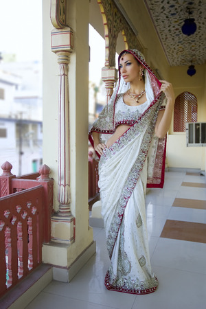 oriental girl: Beautiful young indian woman in traditional clothing with bridal makeup and oriental jewelry. Beautiful Girl bollywood dancer in Sari posing outdoor near the eastern palace