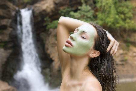antifaz: Spa al aire libre, mujer joven hermosa que miente con la máscara facial verde natural en su cara