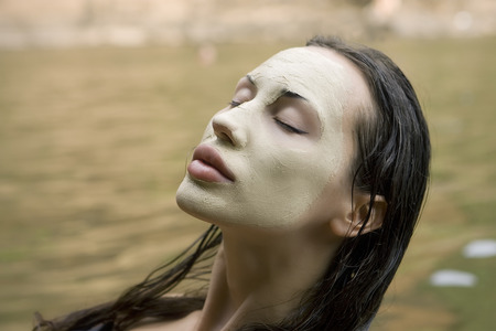 Spa Outdoor, Beautiful young woman lying with natural dead sea facial mask on her face Фото со стока