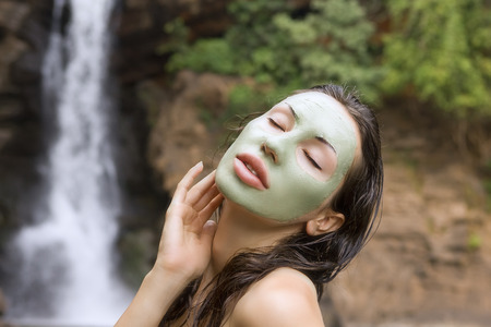 Spa Outdoor, Beautiful young woman lying with natural green herbal facial mask on her face