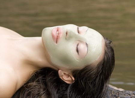 dead sea: Spa Outdoor, Beautiful young woman lying with natural clay facial mask on her face.