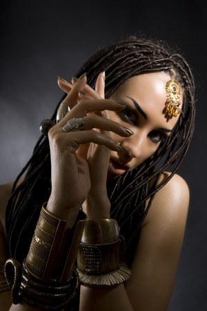 cornrows: Fashion Beauty. Mystic eastern Make-up. Beautiful Woman With Luxury glossy gold Makeup and stylish hair (dreadlocks) . Beautiful sensitive Girl Face, indian accessories (oriental jewelry)