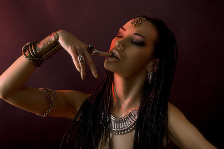 Fashion Beauty. Mystic eastern Make-up. Beautiful Woman With Luxury glossy gold Makeup and stylish hair (dreadlocks) . Beautiful sensitive Girl Face, indian accessories (oriental jewelry)