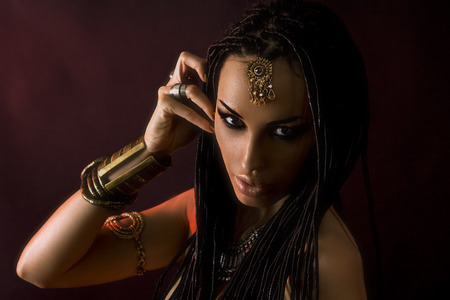 succubus: Fashion Beauty. Mystic eastern Make-up. Beautiful Woman With Luxury glossy gold Makeup and stylish hair (dreadlocks) . Beautiful sensitive Girl Face, indian accessories (oriental jewelry)