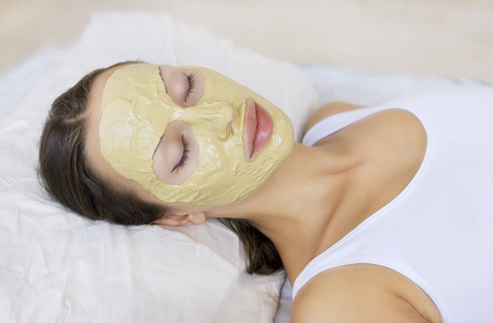 day care: Spa Outdoor, Beautiful young woman lying with natural Indian Multani Matti clay facial mask on her face, skin care and wellness Stock Photo