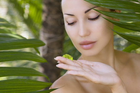 Beautiful caucasian woman holding natural aloe vera facial gel, skin care and wellness. Facial moisturize mask, spa salon outdoors.