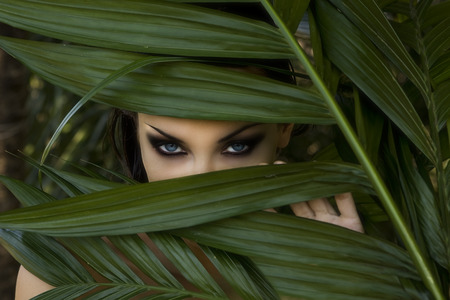 Sexy beautiful woman hiding behind the palm leaves like a panther in the in the tropical forest in India. Portrait of beautiful caucasian stylish young woman with smokey eyes, wildness Stock Photo