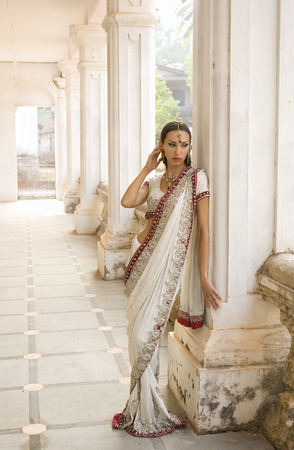 indian saree: Beautiful young indian woman in traditional clothing with bridal makeup and oriental jewelry. Beautiful Girl bollywood dancer in Sari posing outdoor near the eastern palace