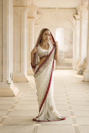indian saree: Beautiful young indian woman in traditional clothing with bridal makeup and oriental jewelry. Girl bollywood dancer in Sari posing outdoor near the eastern palace. Eastern fairy tale