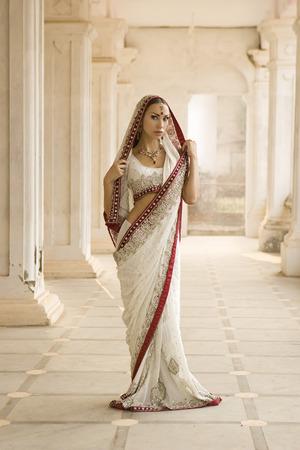 fille indienne: Belle jeune femme en costume traditionnel indien avec maquillage de mariée et de bijoux oriental. Fille bollywood danseur dans Sari posant en plein air près du palais de l'Est. Conte de fée de l'Est