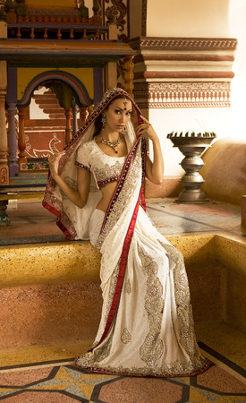 sari: Beautiful young indian woman in traditional clothing with bridal makeup and oriental jewelry. Girl bollywood dancer in Sari posing outdoor near the eastern palace. Eastern fairy tale